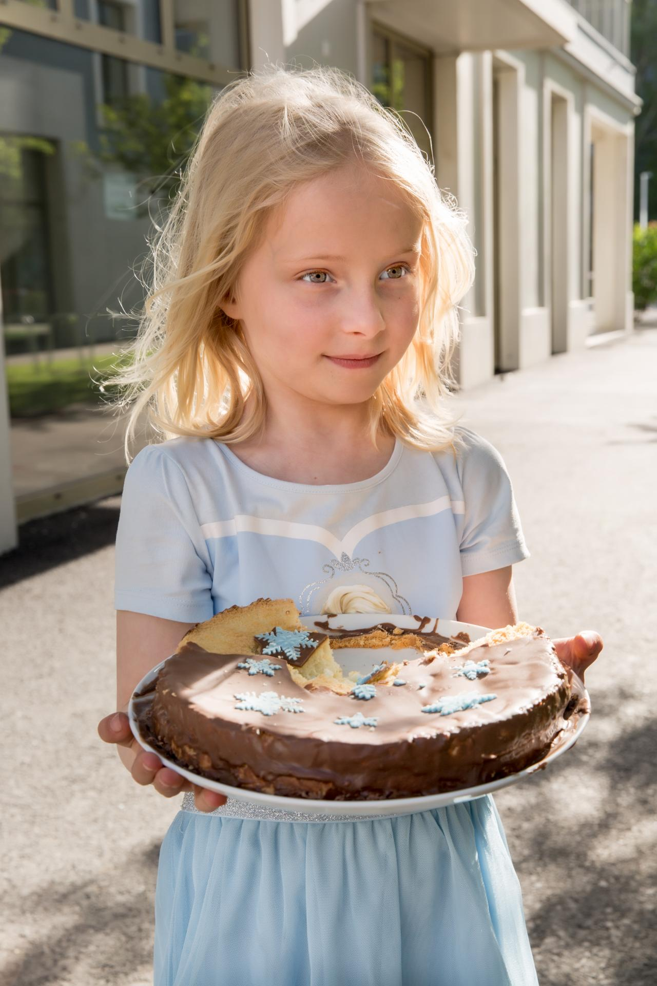 Girl with birthday cake, sunlight